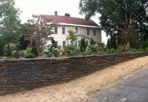 The trees and shrubs of the newly planted border revealing framed views of the house